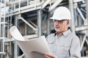 Engineer wearing hardhat reading plans